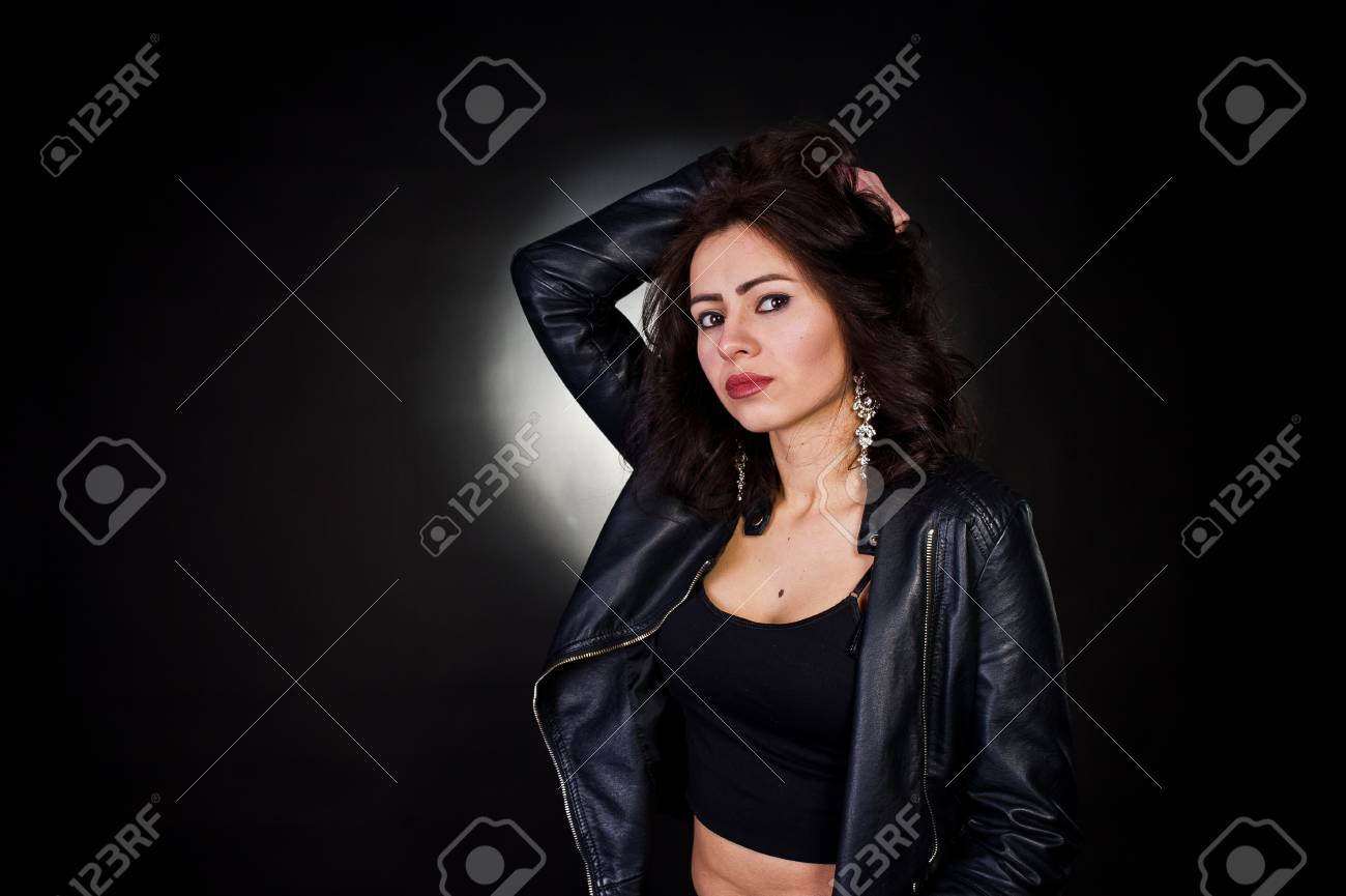Stock photo studio portrait of sexy brunette girl in black leather jacket against black background