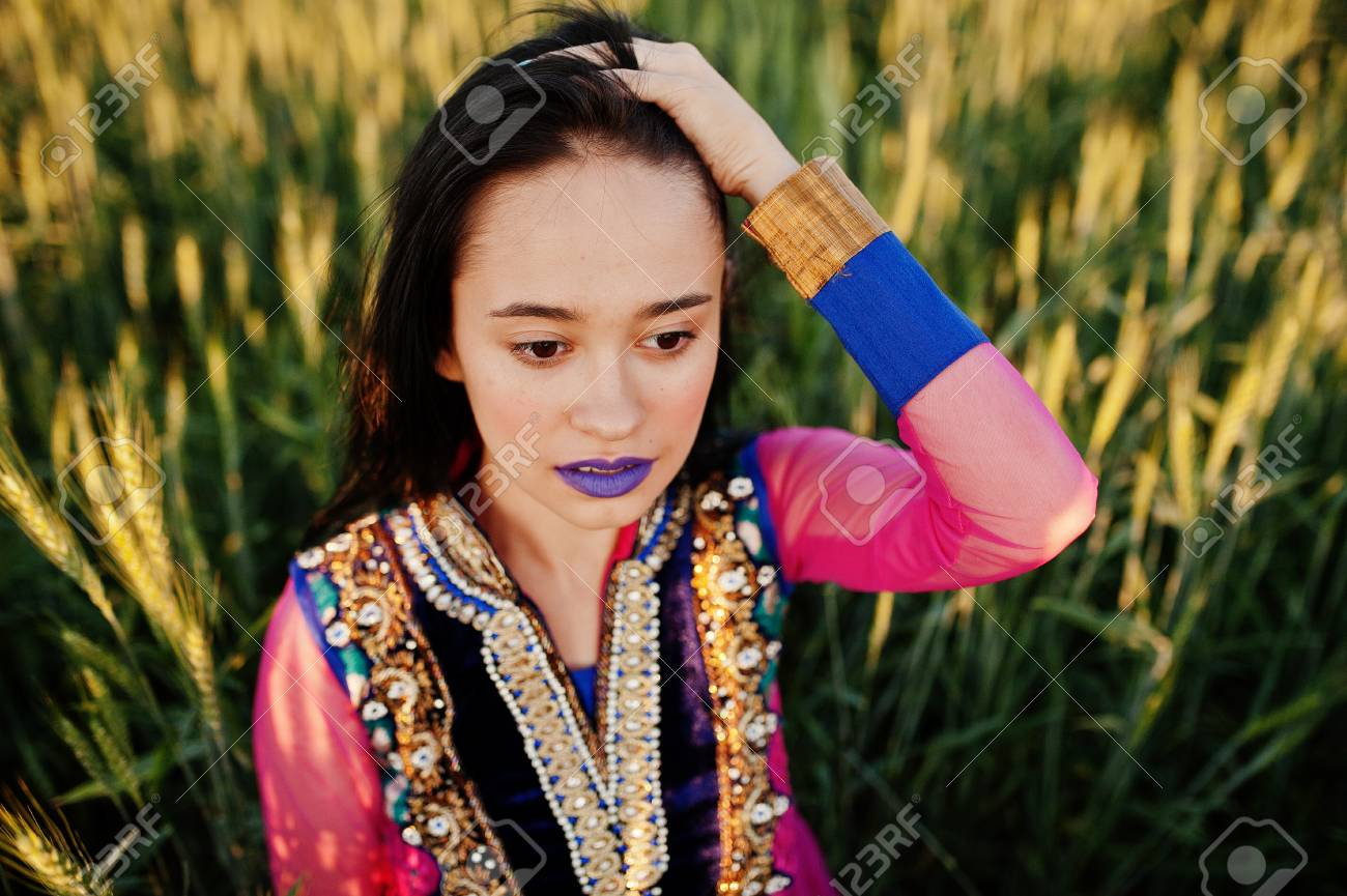Stock Photo - Tender indian girl in saree, with violet lips make up posed  at field in sunset. Fashionable india model.