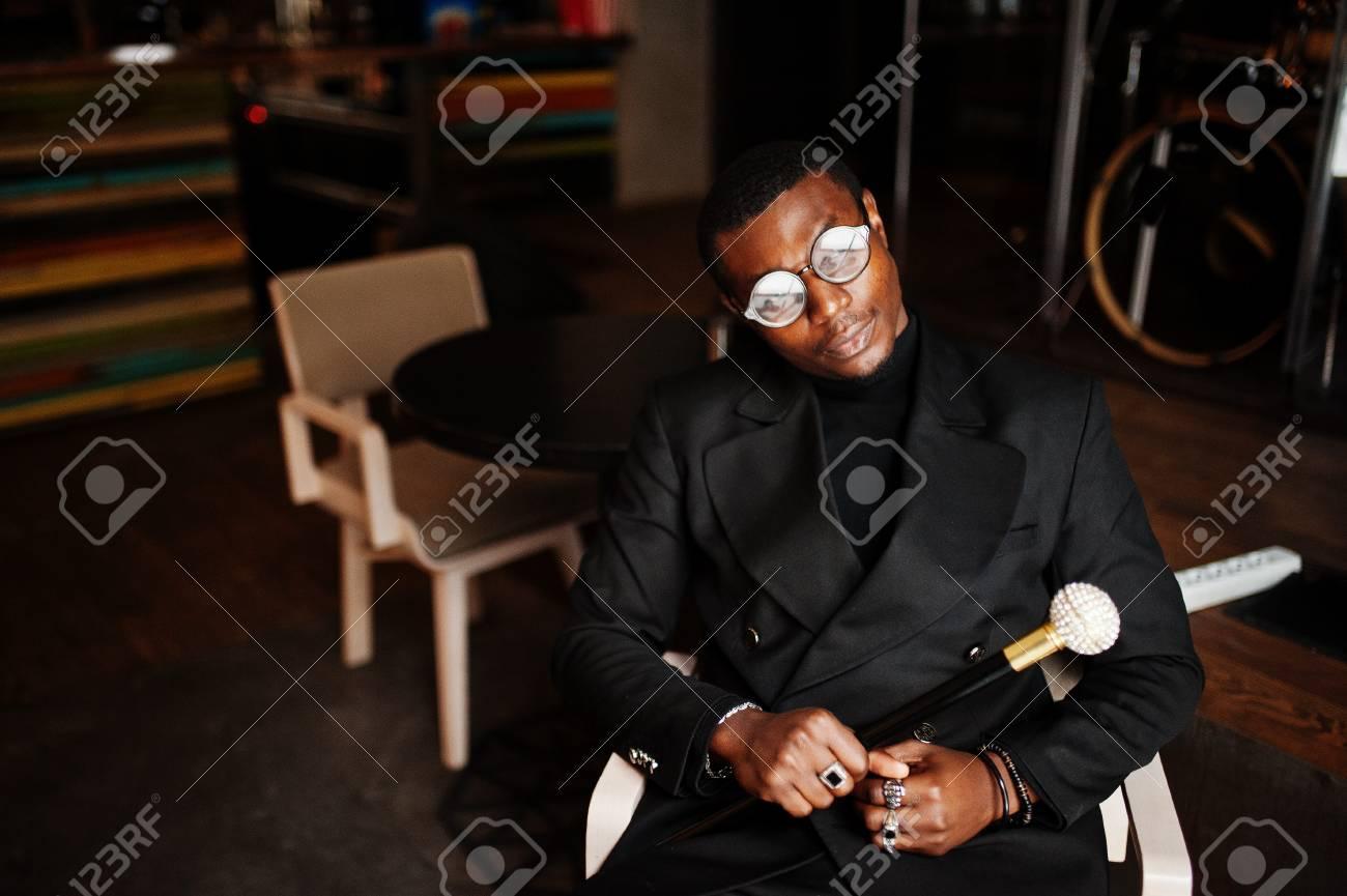 Stylish african american gentleman in elegant black jacket and glasses - 115861339