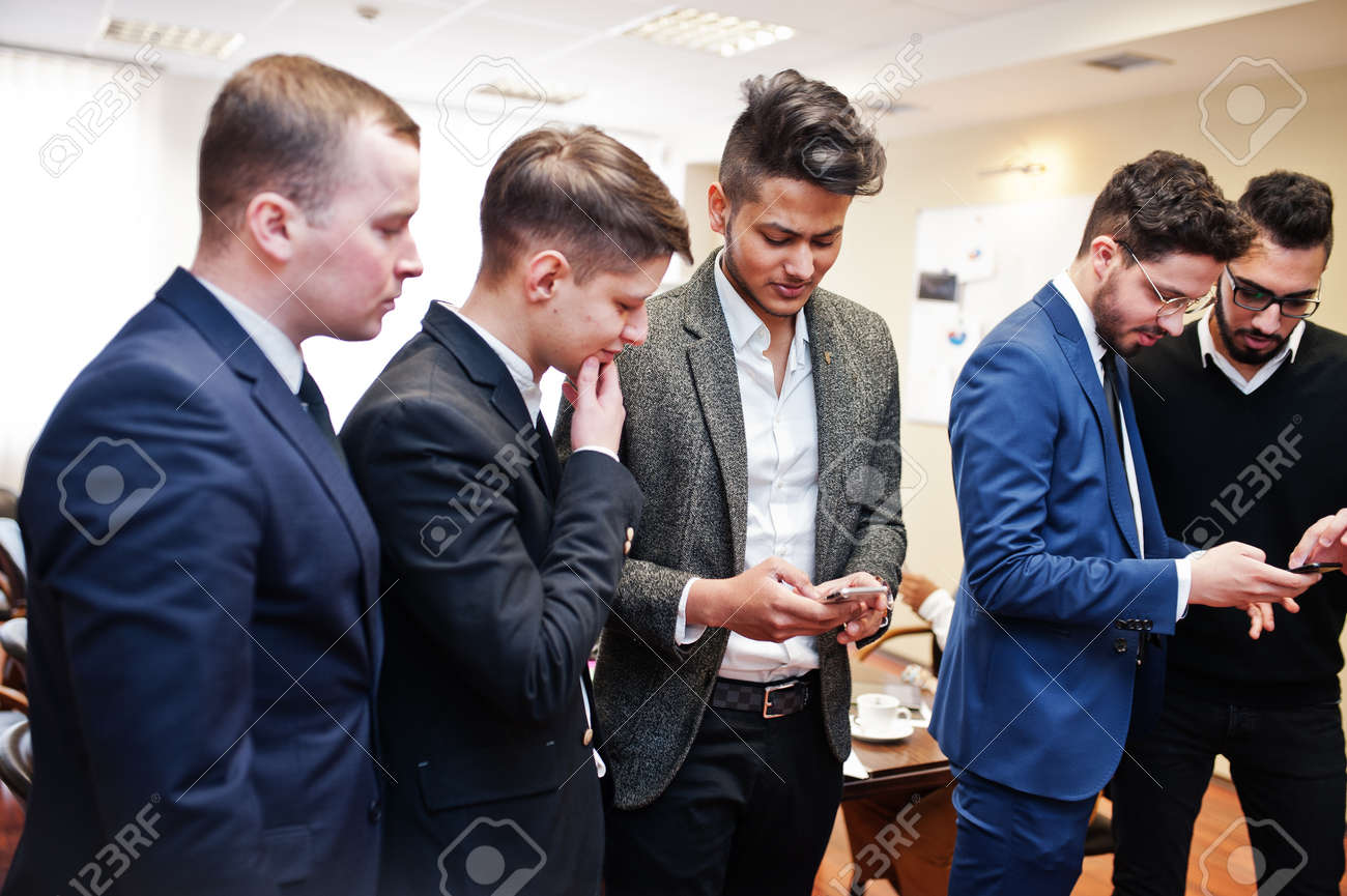Six multiracial business mans standing at office and use mobile phones. Diverse group of male employees in formal wear with cellphones. - 122309299