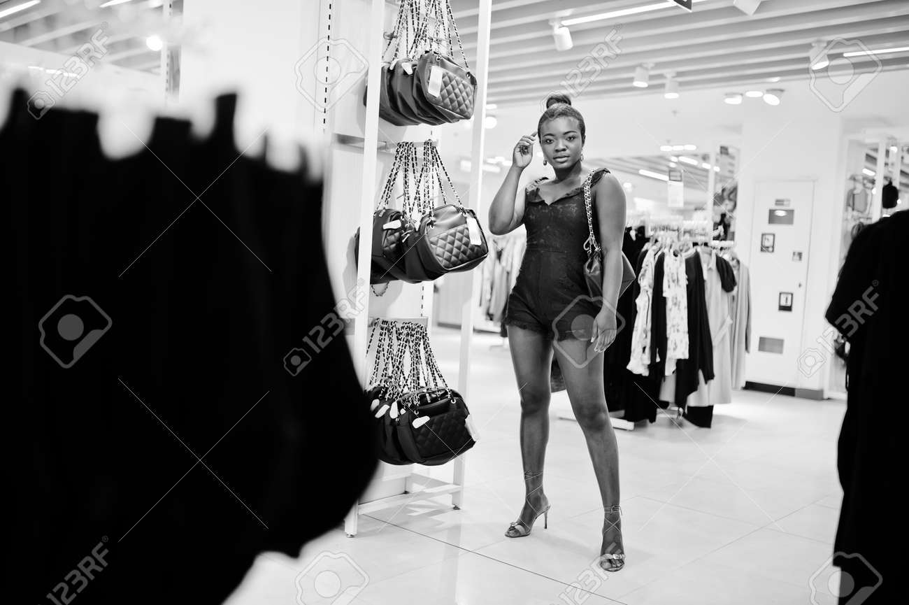Young fashionable and afro woman in green combidress shopping at clothes store. She choose handbag. - 125649310