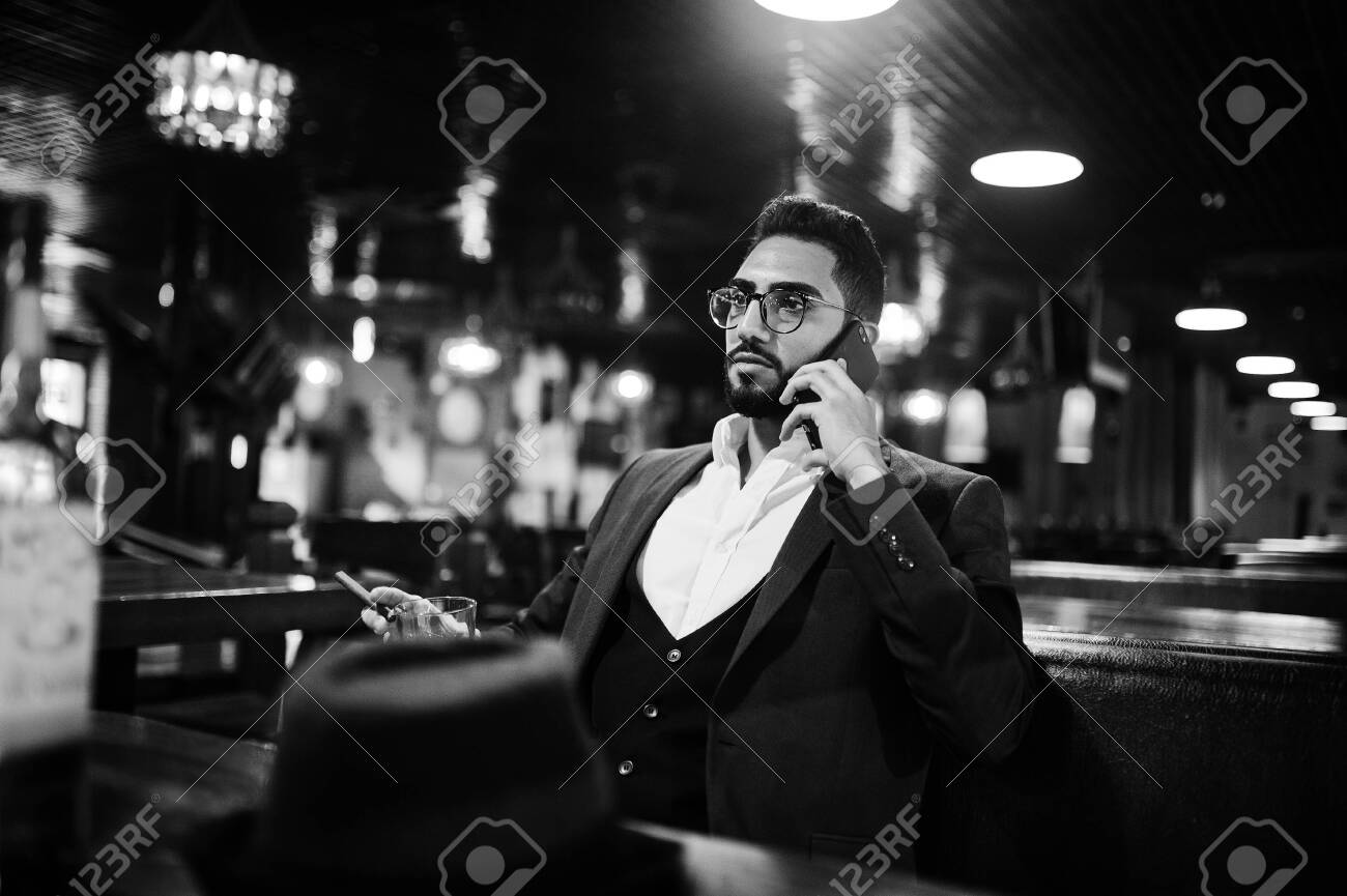 Handsome well-dressed arabian man with glass of whiskey and cigar hold mobile phone, posed at pub. - 131317453