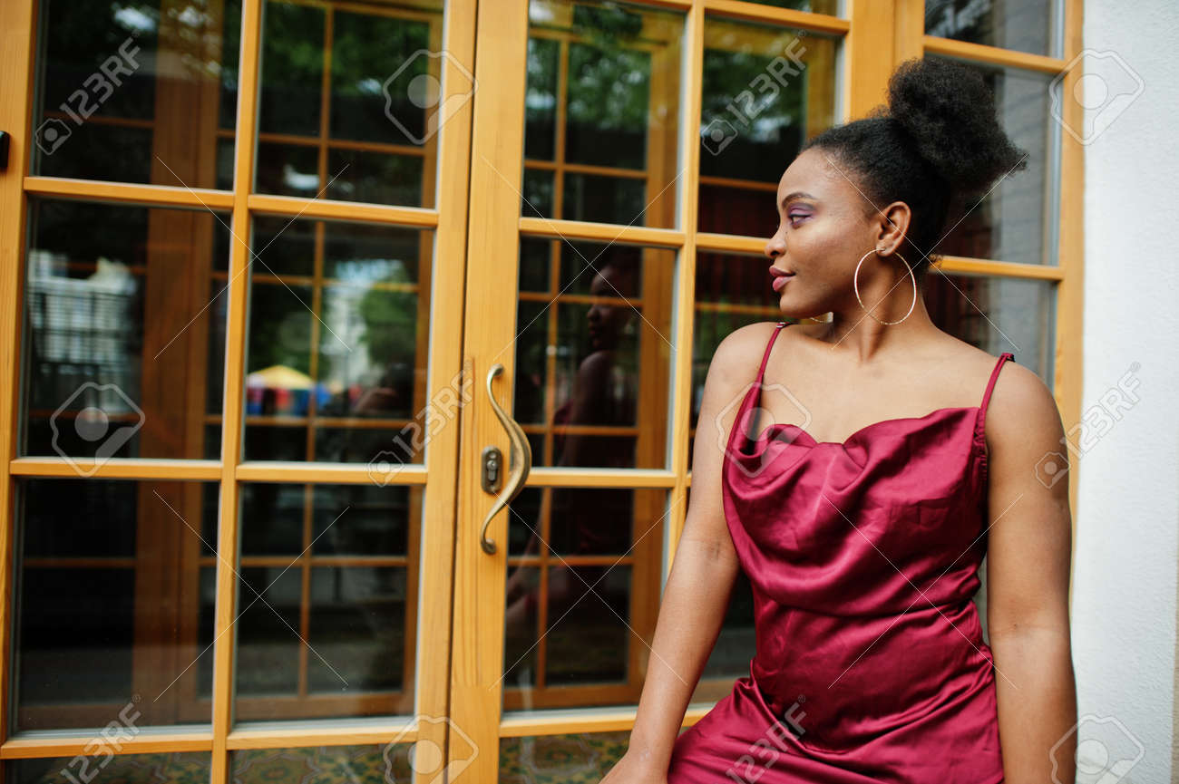Portrait of a beautiful natural young African woman with afro hair. Black model in red silk dress. - 158421108