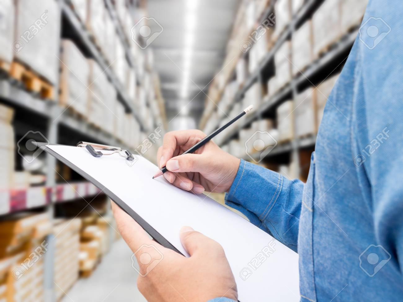 Man checking list on clipboard in a warehouse - 88438320