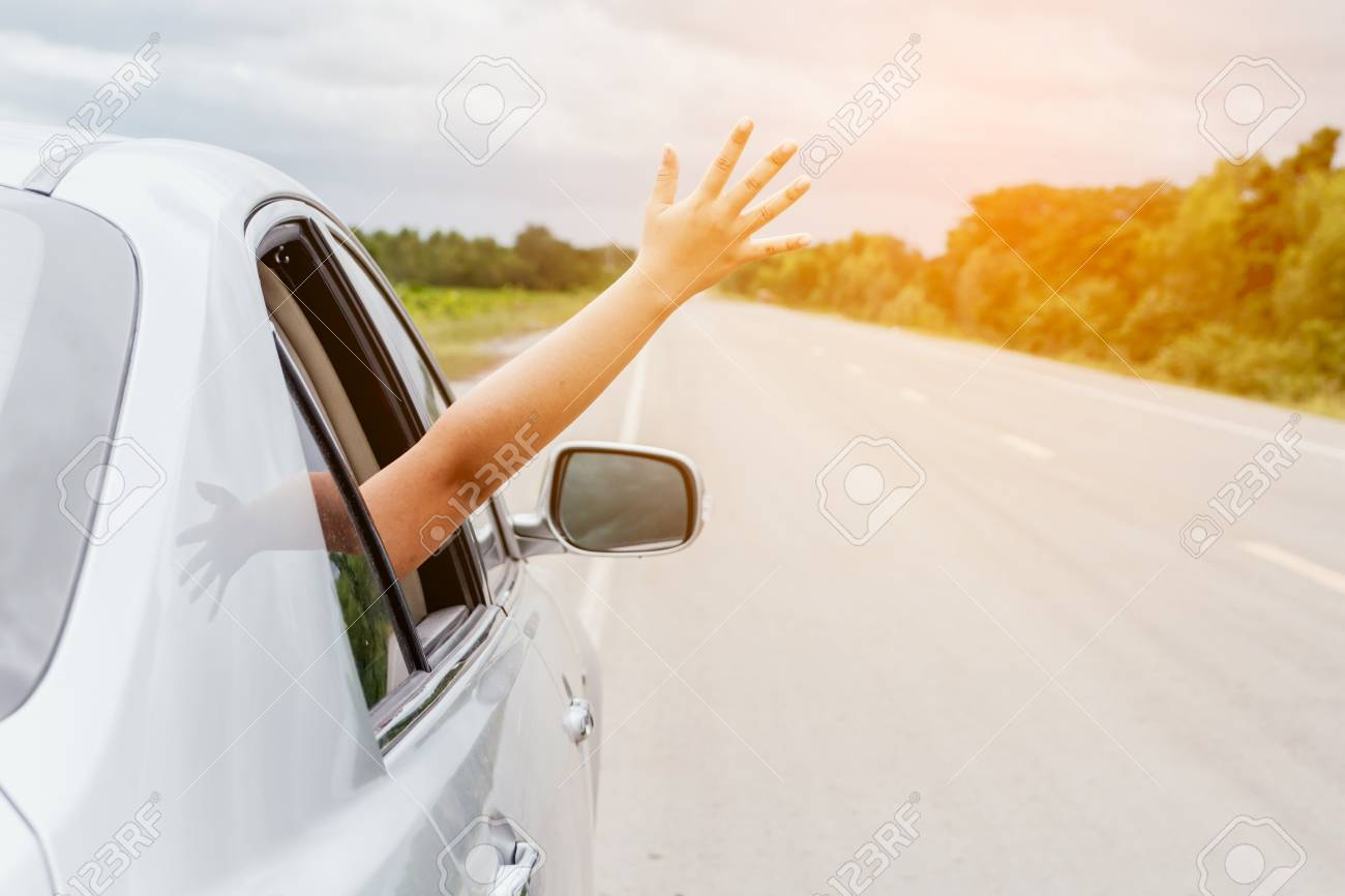 Woman hand in the car relaxing and happy traveler on the road - 97328515