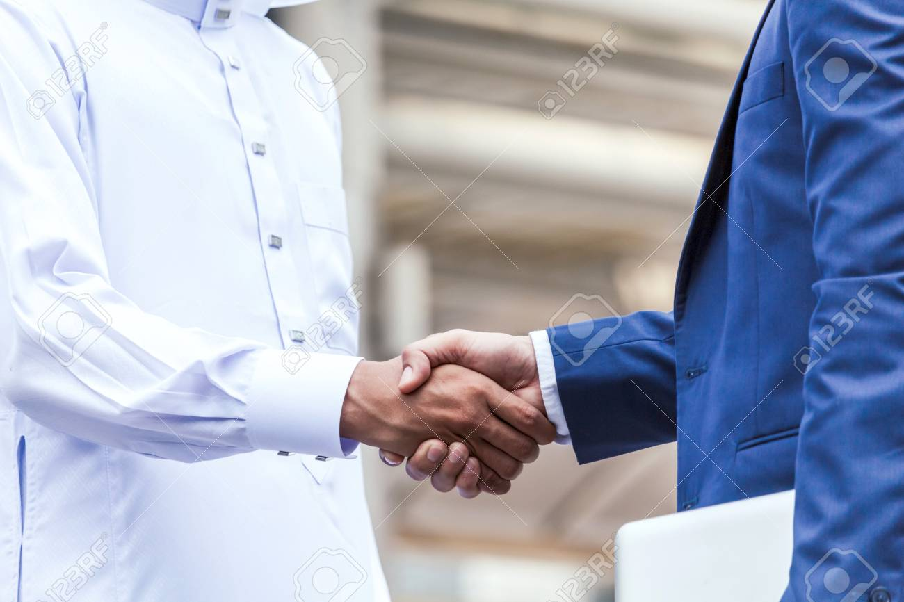 Successful businessmen handshake partner with arab businessman - 98984520