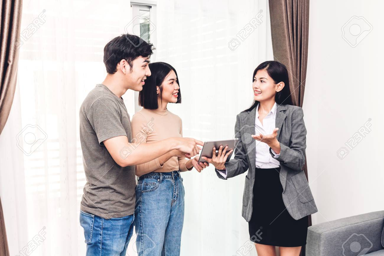 Real estate agent holding tablet and talk with young couple in a house for sale. business and real estate concept - 108531548