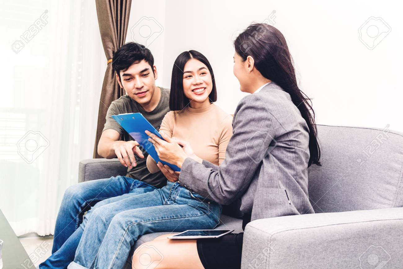 Real estate agent holding documents to sign agreement paper to couple for signature in a house for sale.Young couple signing contract.business and real estate concept - 108749541