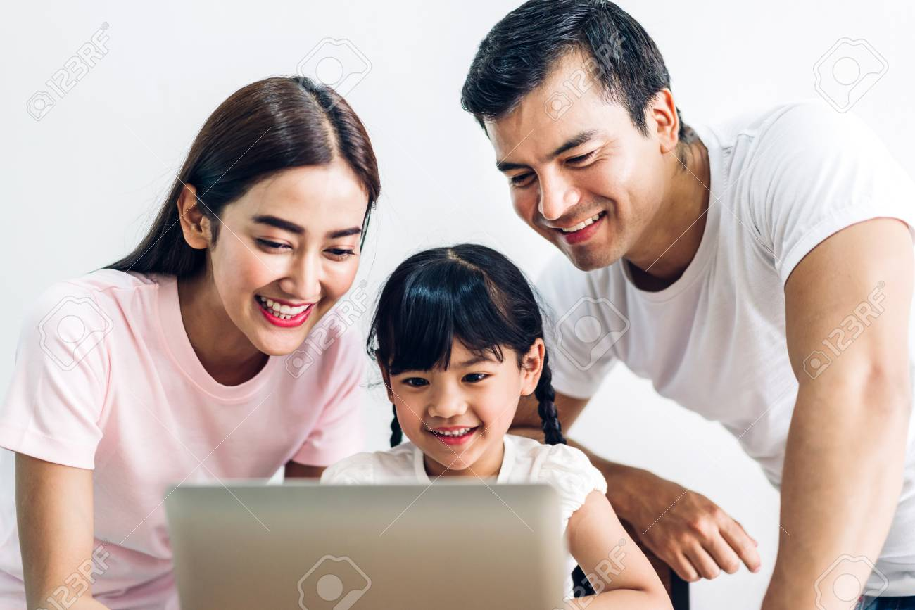 Happy family father and mother with daughter sitting and looking at laptop computer together in the living room at home - 122243353