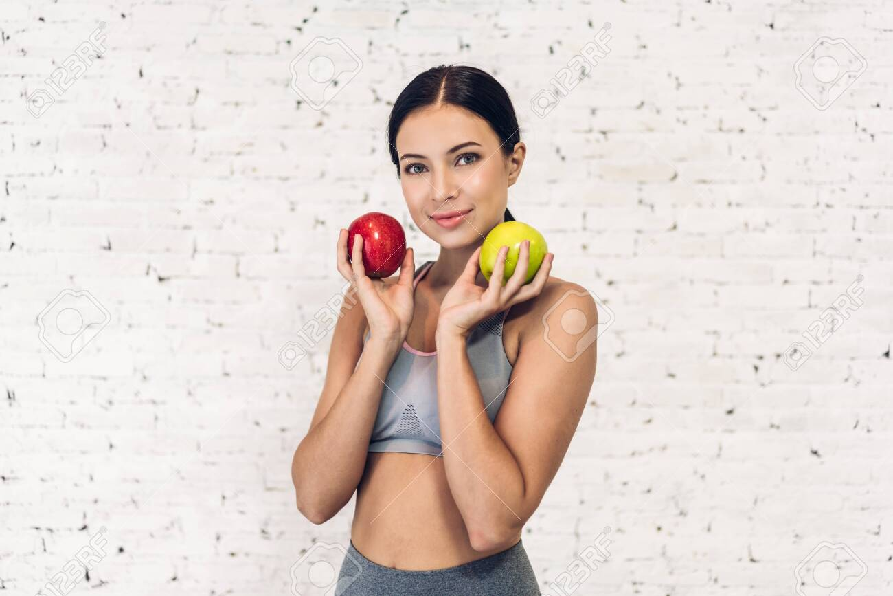 Sport healthy woman holding a red apple isolated on white wall background - 154473152