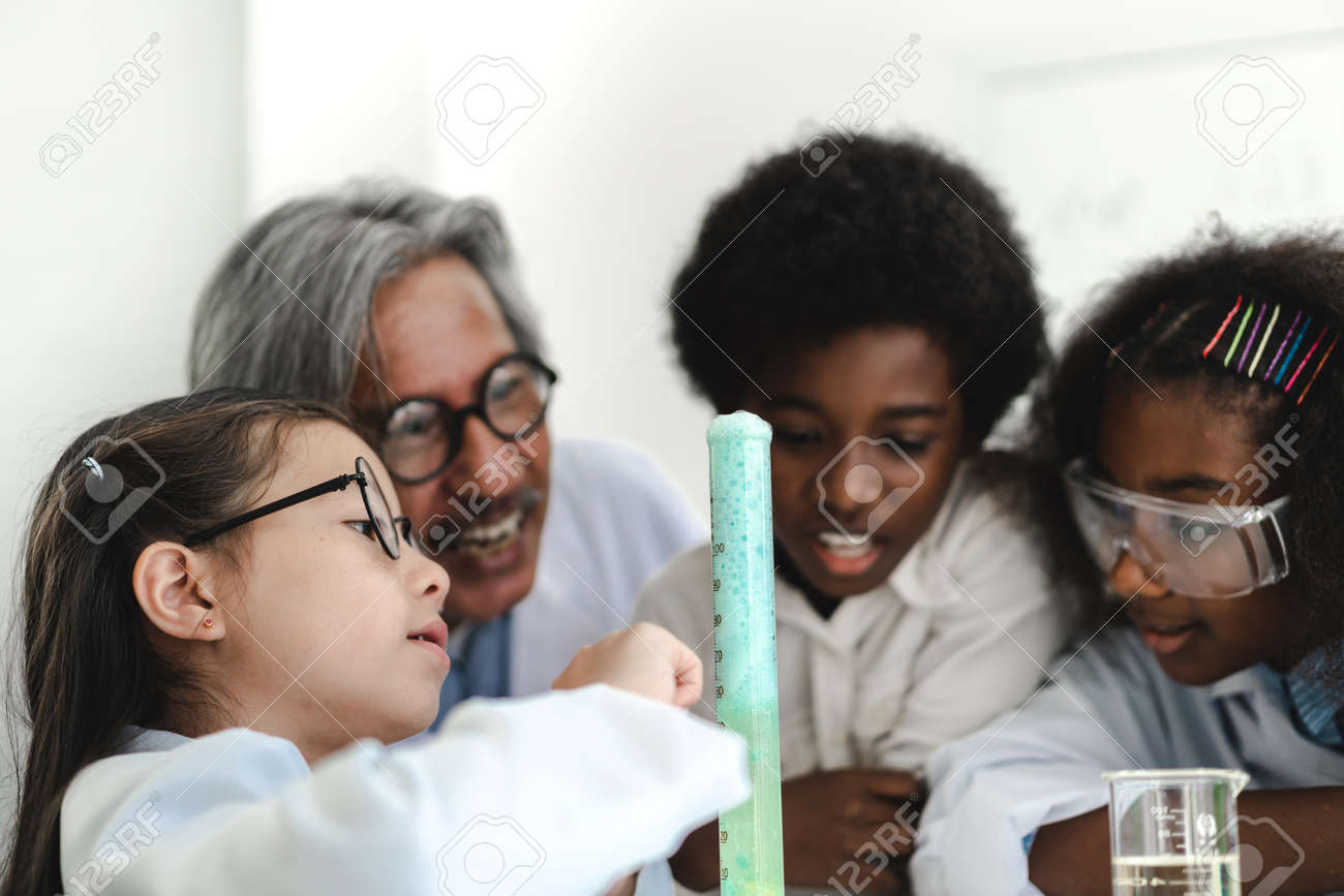 Group of teenage students learning and doing a chemical experiment and holding test tube in hands in the experiment laboratory class on table at school.Education concept - 168607001