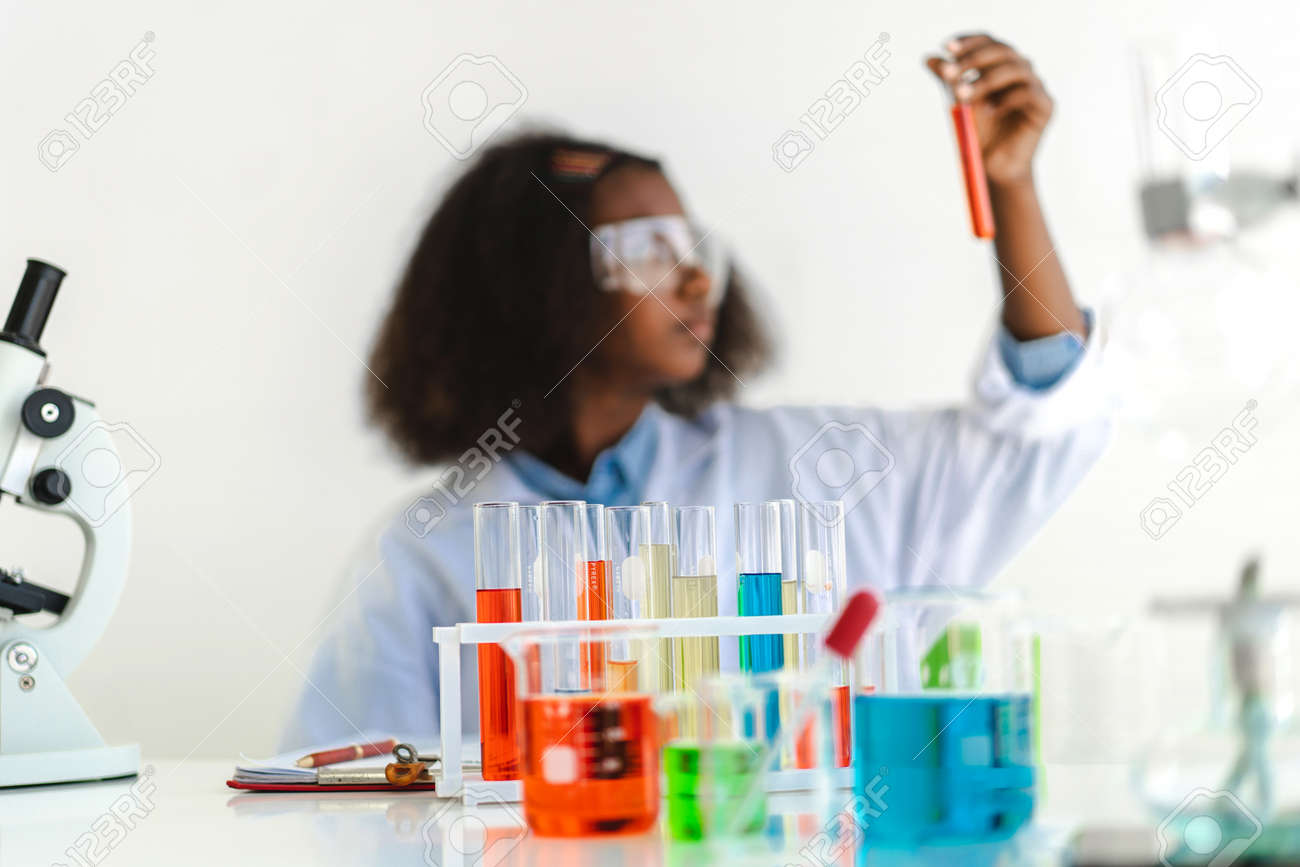 African american girl students learning and doing a chemical experiment and holding test tube in hands in science class on the table.Education concept - 168607007