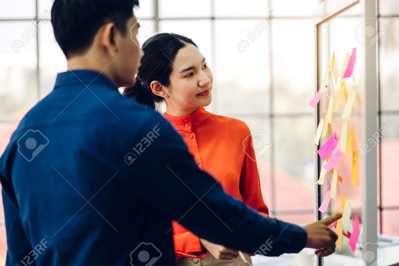 Two casual business people planning and brainstorm writing over the project with stickers note on glass window at modern office.Teamwork concept - 168607137