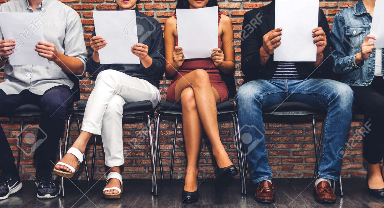Group of business people holding paper while sitting on chair waiting for job interview against wall background - 168607144