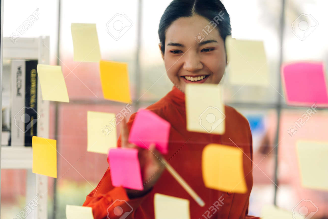 Casual business woman planning and working writing over the project with stickers note on glass window at modern office - 168607223