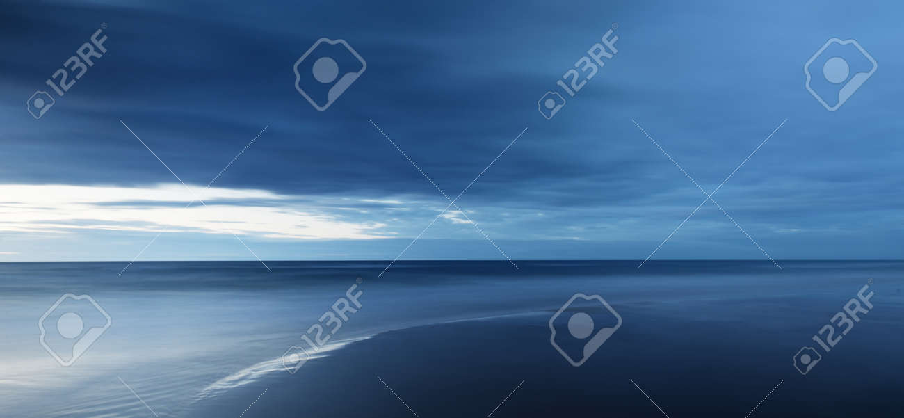 Baltic sea at sunset. Dramatic twilight sky, blue glowing clouds. Waves, splashing water. Picturesque scenery, seascape, cloudscape, nature. Panoramic view, long exposure - 166536597