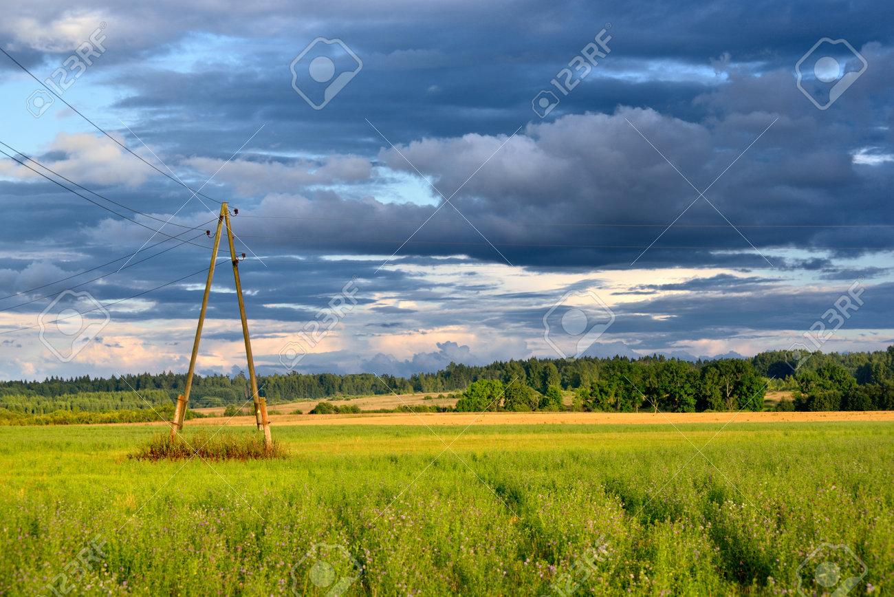 Green field against dark stormy clouds - 168298421