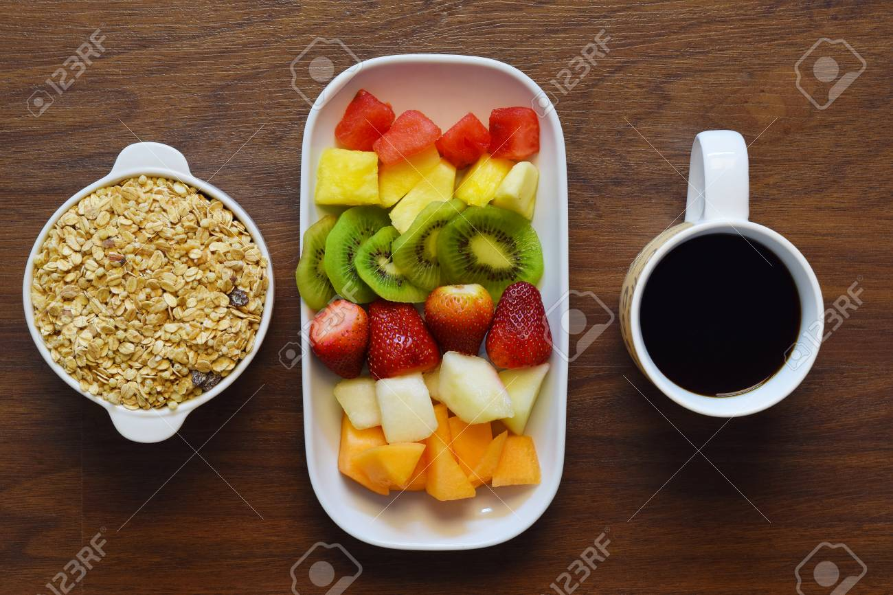 Bowl Of Granola Fruit Platter And Cup Of Coffee On A Wooden Stock Photo Picture And Royalty Free Image Image 62719010