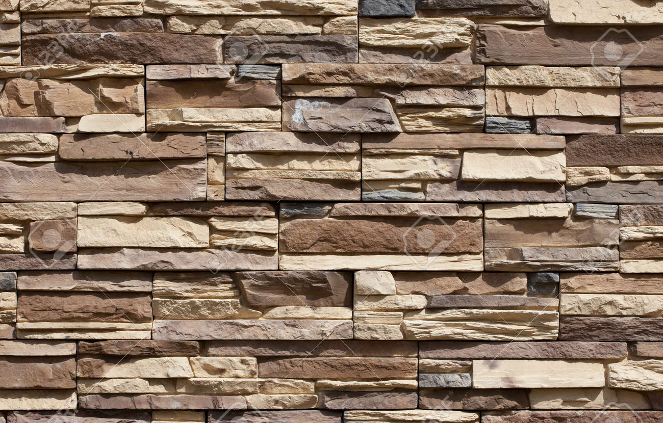 fragment of beige stone wall stock photo