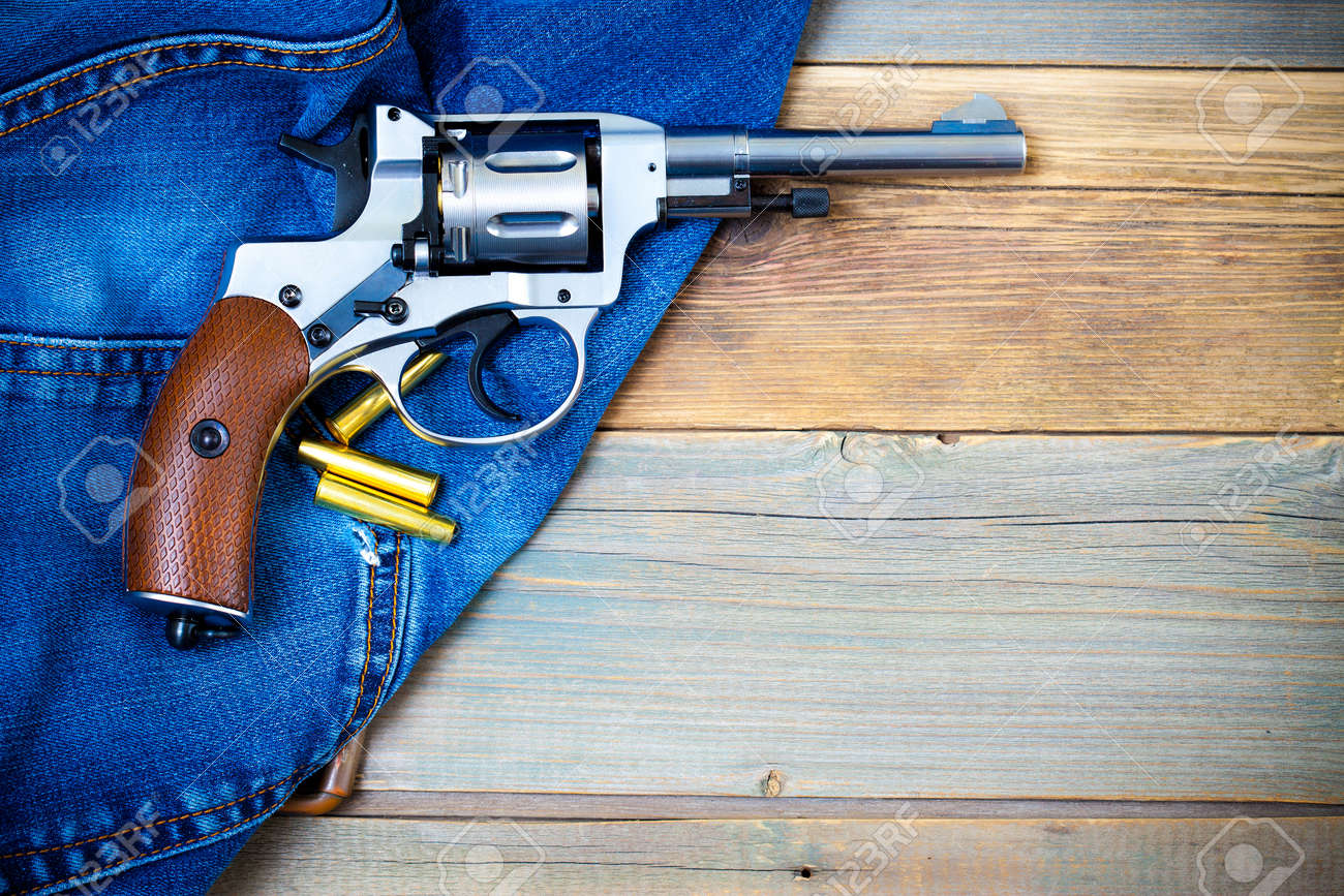 revolver nagant with cartridges on old jeans background with