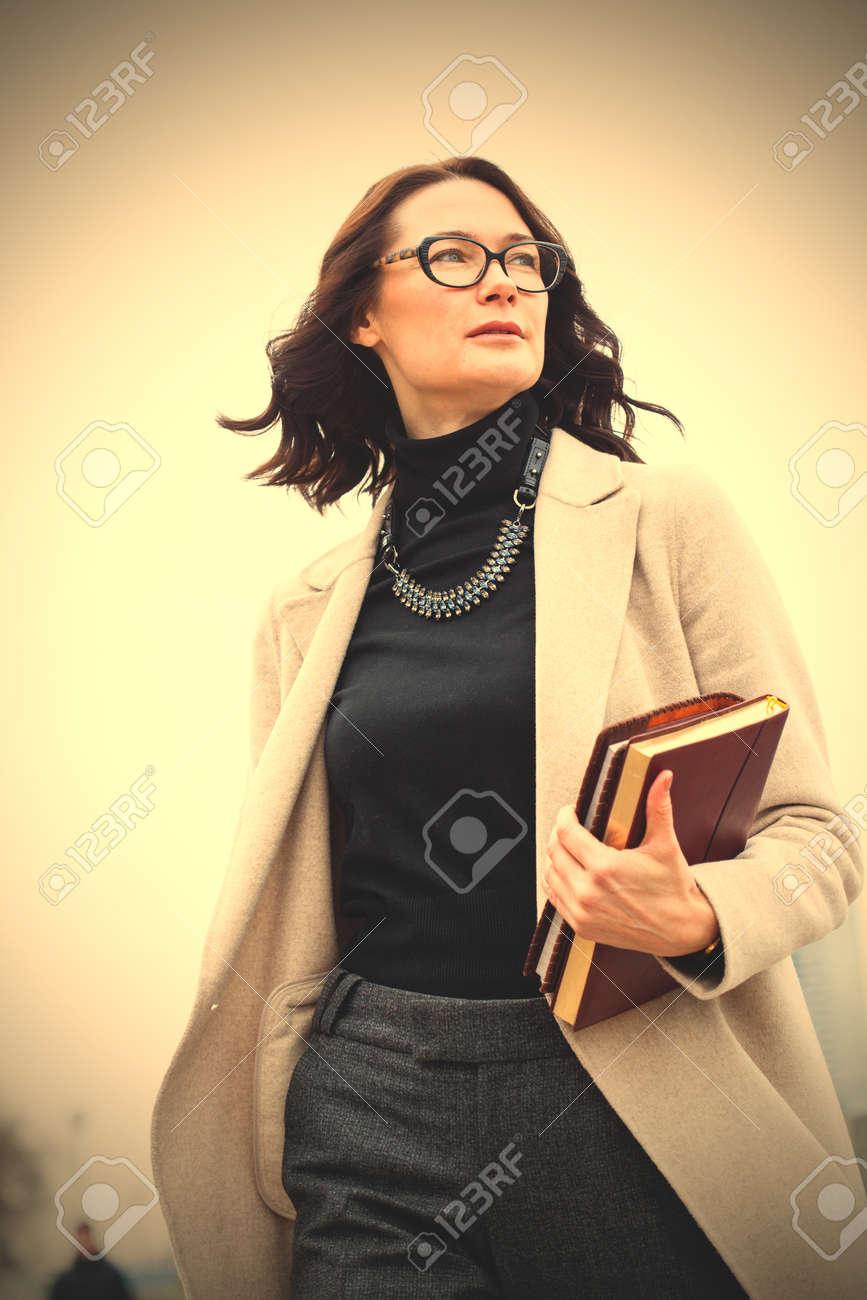 Bella donna di mezza età dai capelli scuri in un cappotto luminoso e con i libri nelle loro mani. filtro immagine stile retrò