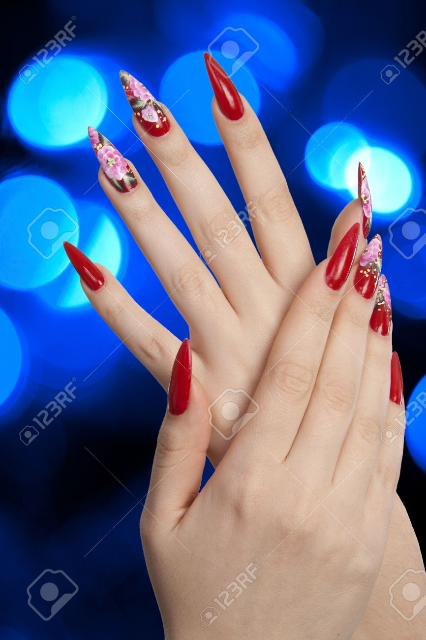 Girl fingers with beautiful drawing on nails over abstract spots of blue lights Stock Photo - 10474944