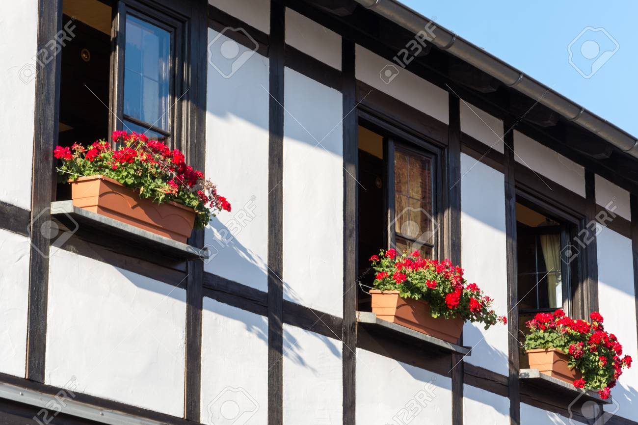 Half Timbered House With Window Shutters And Colorful Flowers