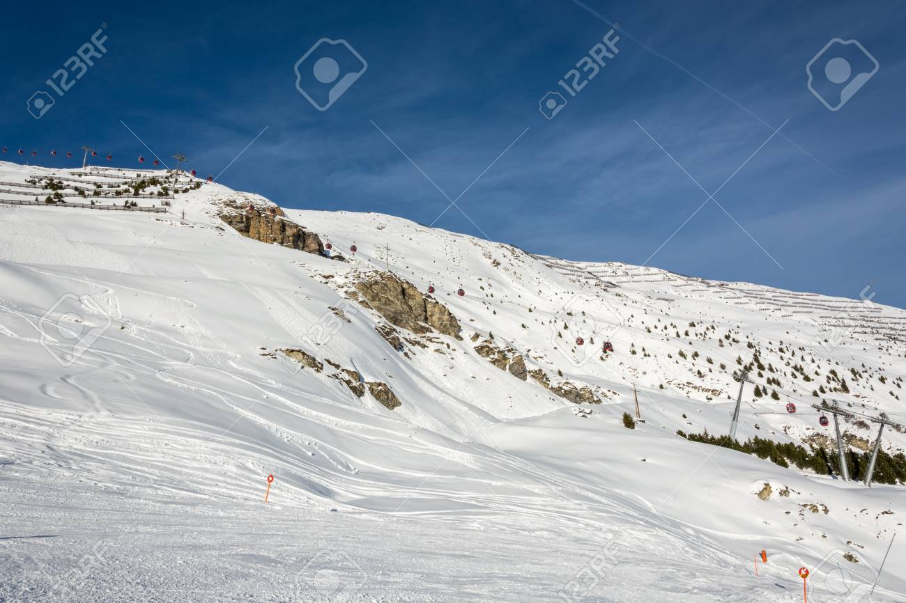 slope and red gondolas in ski resort serfaus fiss ladis in austria