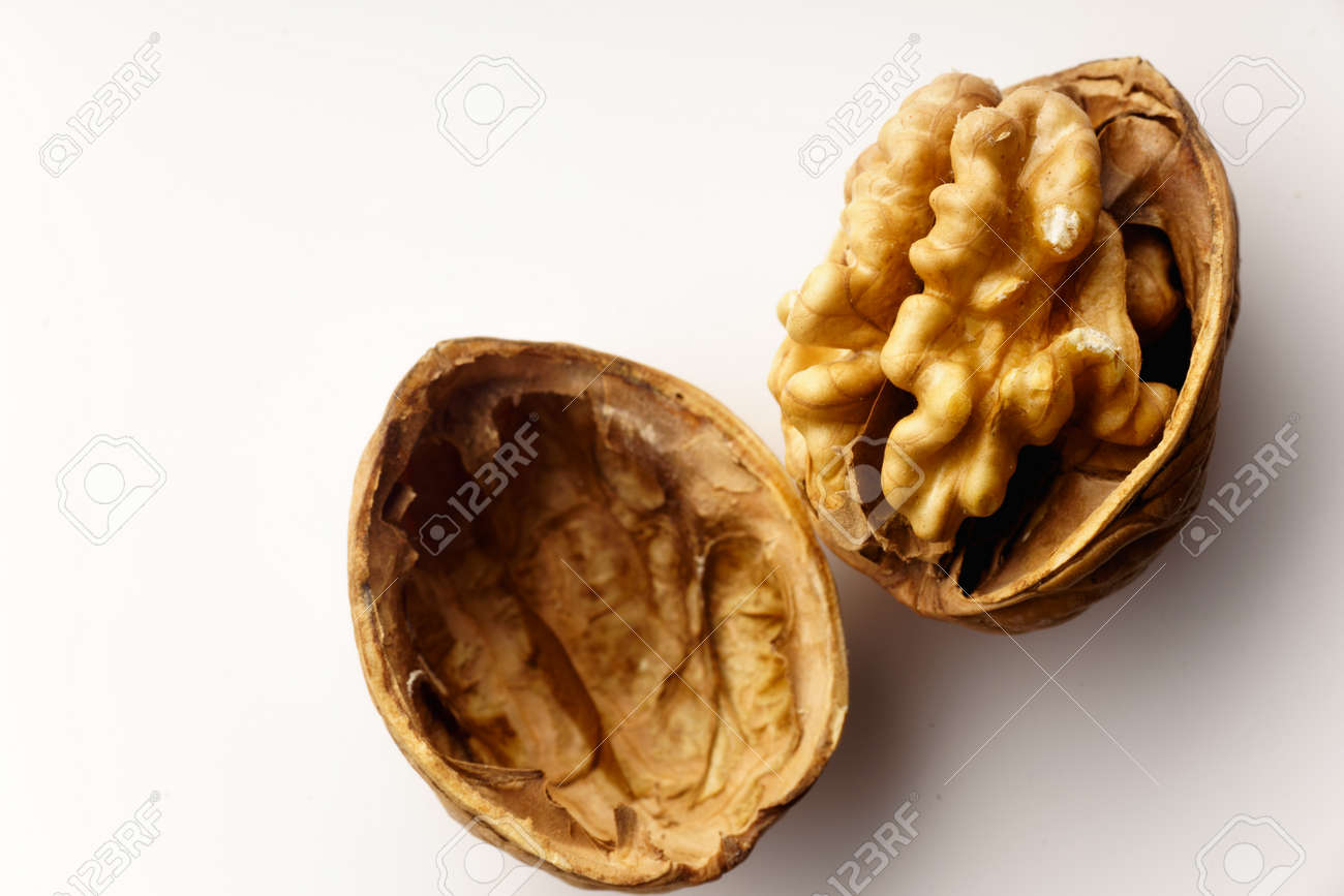 Raw walnuts with cracked nutshells on white background isolated with copy space - 142409713