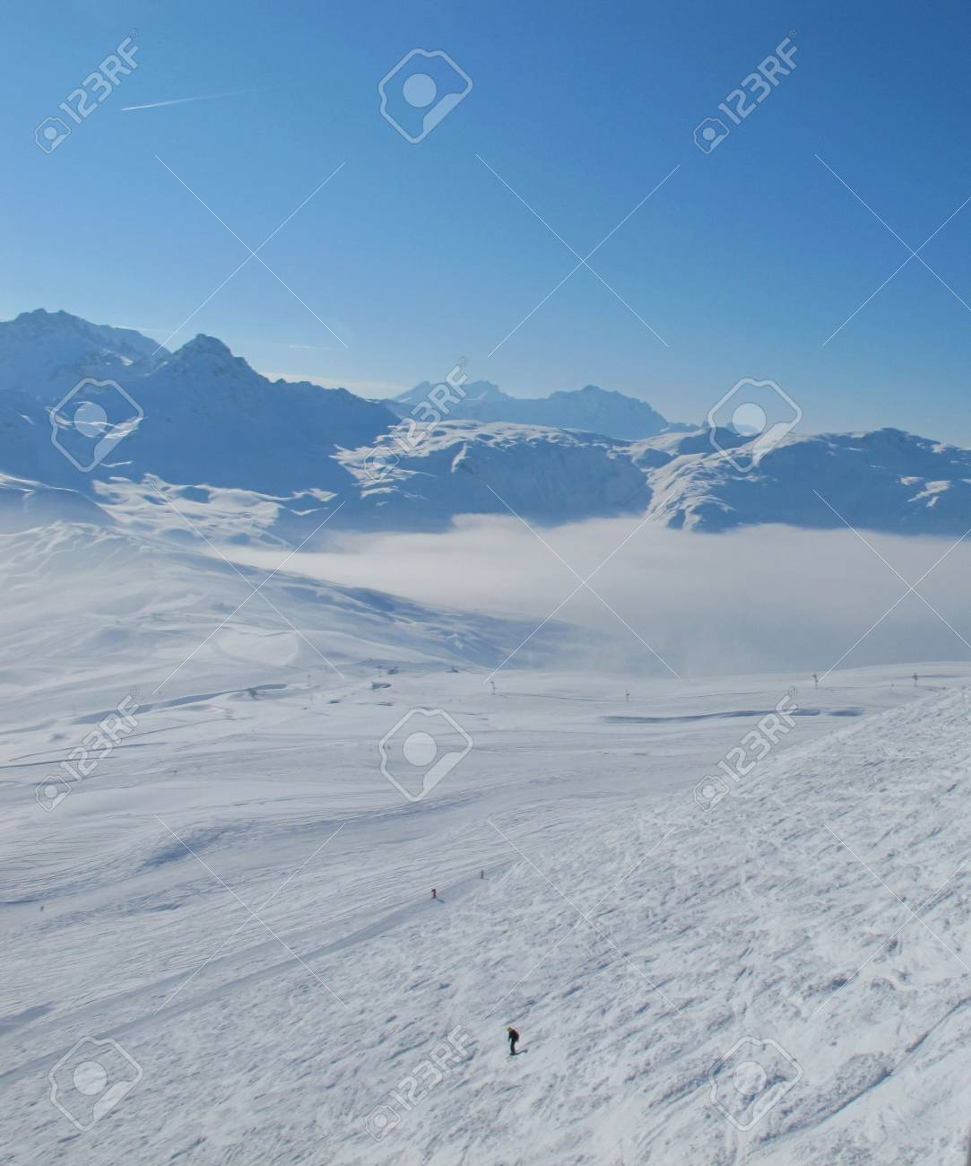Lone skier. French alp mountains and clouds in valleys. Skiing Les Contamines, French alps Stock Photo - 8031654