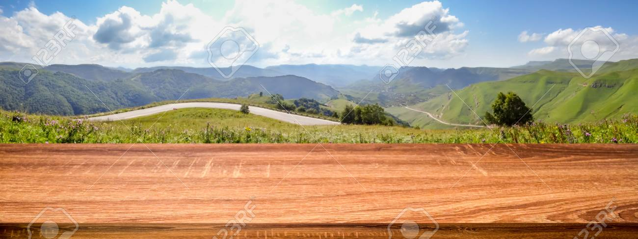 Empty wooden table with blurred panoramic background of summer empty wooden table with blurred panoramic background of summer landscape with road and mountain village voltagebd Images