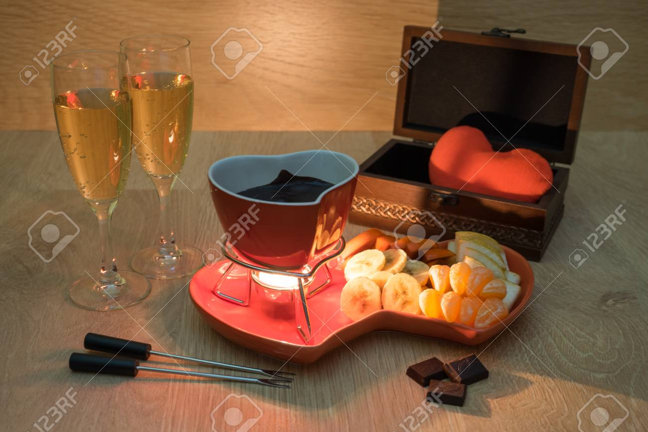 Chocolate fondue with fruit and champagne and a gift with love Stock Photo - 96147539