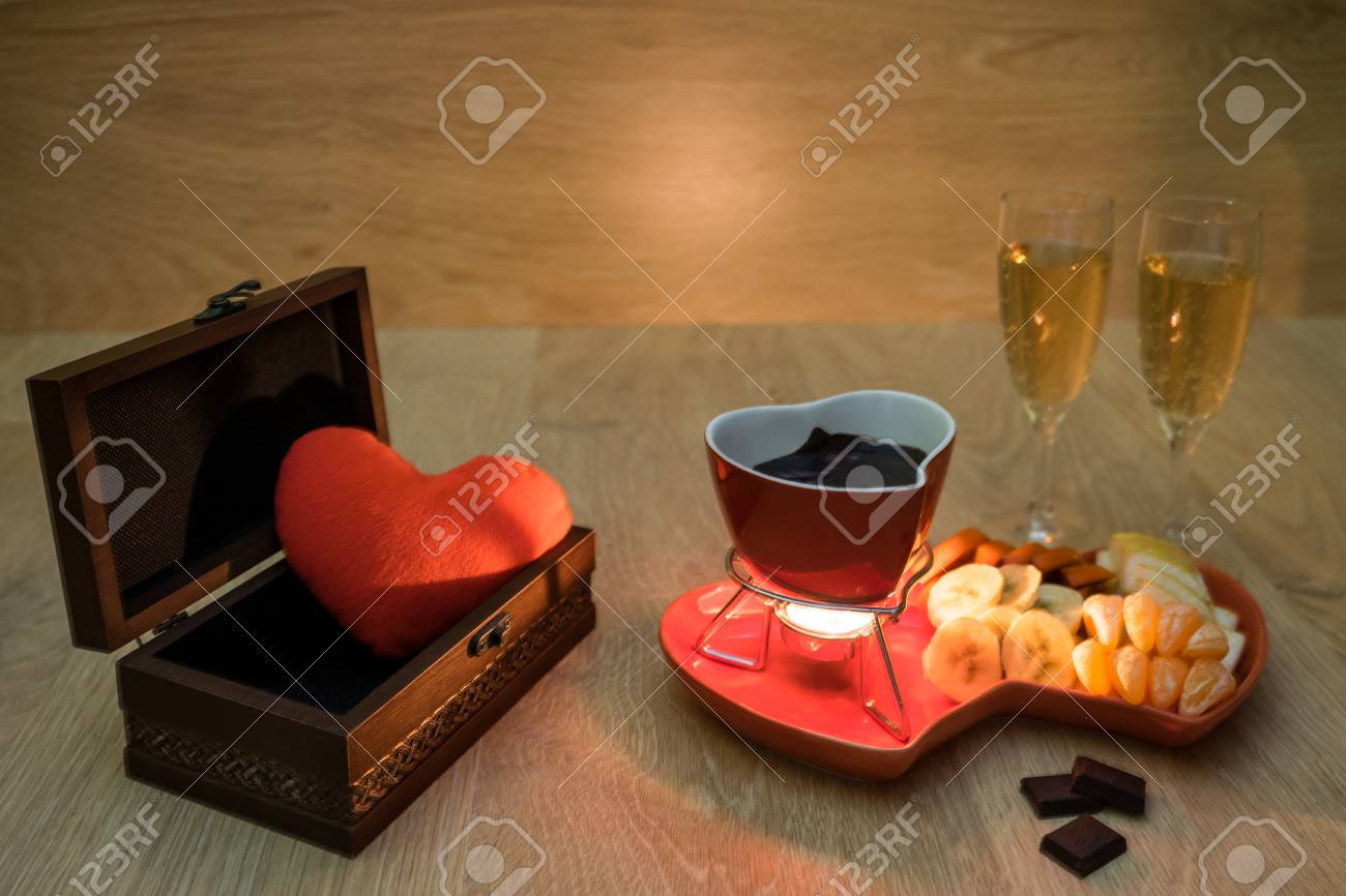 Chocolate fondue with fruit and champagne and a gift with love Stock Photo - 96147540