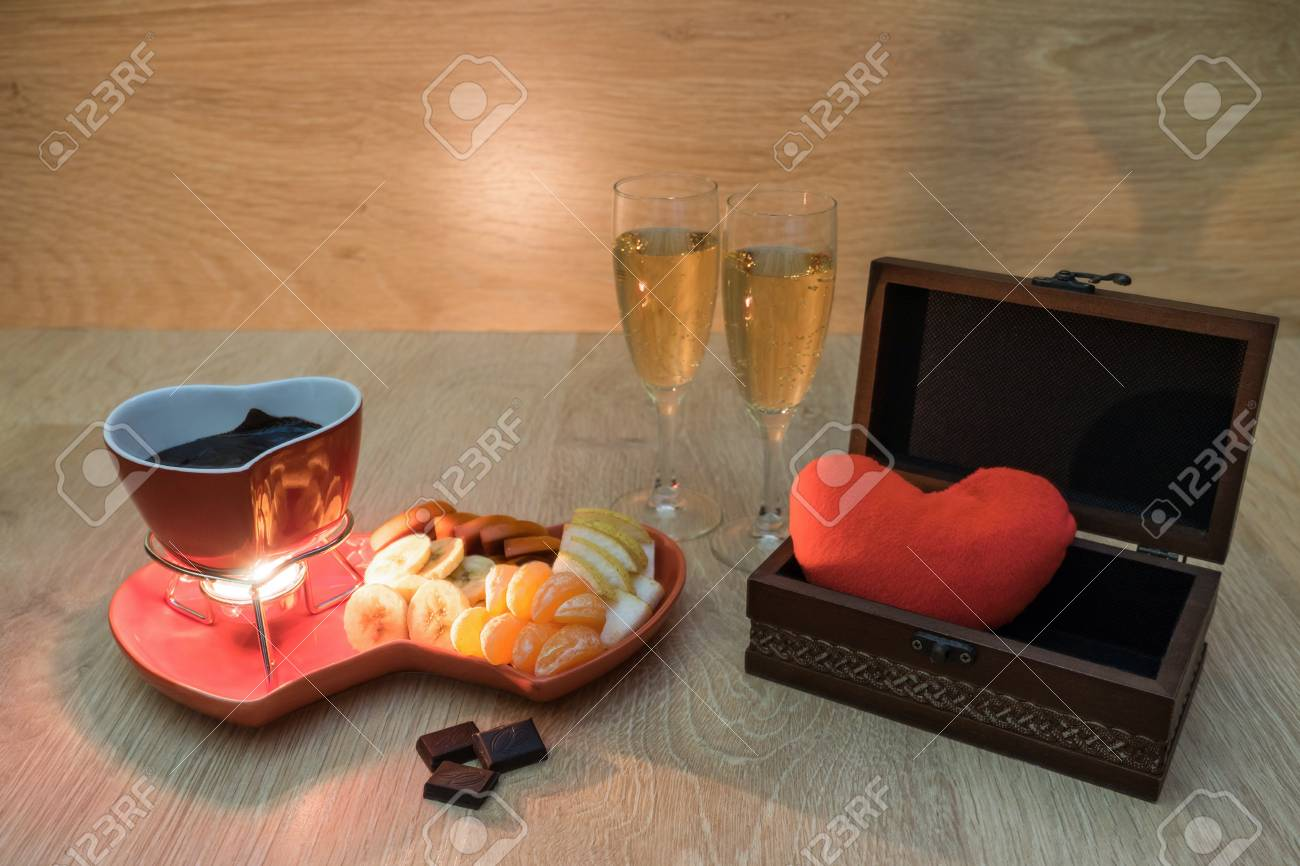 Chocolate fondue with fruit and champagne and a gift box with heart. Romantic dinner.