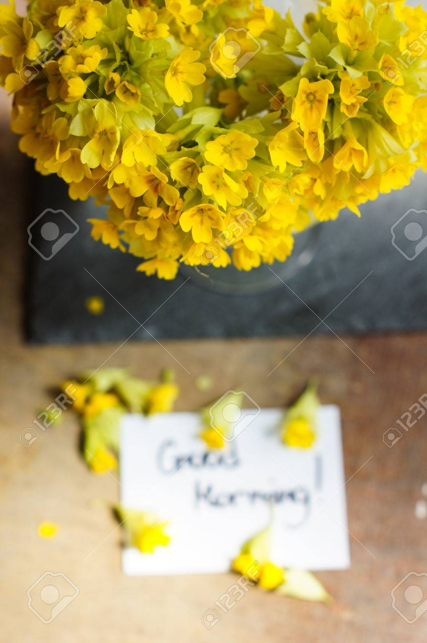First Spring Flowers On The Table With Good Morning Note Stock Photo