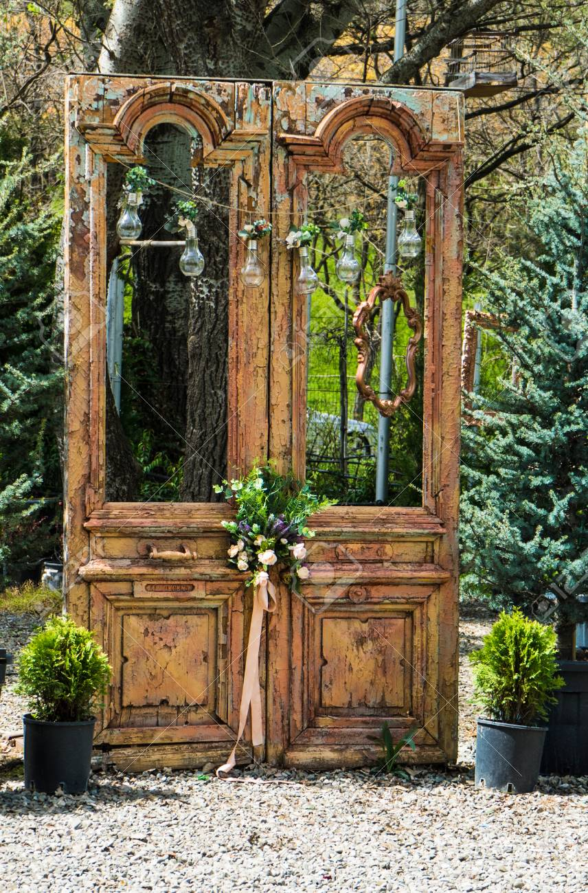 Stock Photo - Wooden wedding doors decorated by white cloth and flowers with greenery with green yard on backdrop. Wedding. Decor & Wooden Wedding Doors Decorated By White Cloth And Flowers With ...