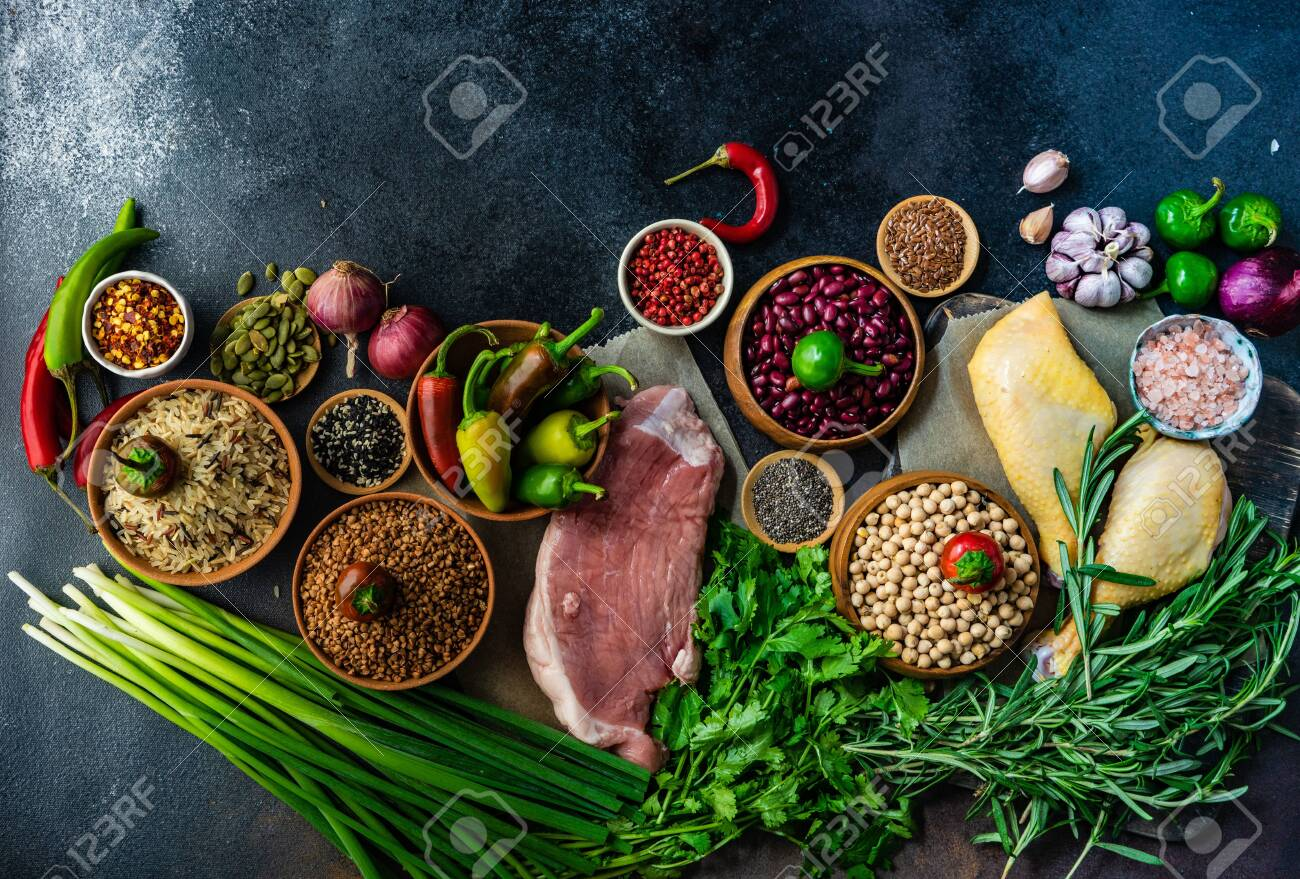 OrganicHealthy with organic vegetables, herbs, raw meat, seeds and cereals on stone background with copy space - 129307686