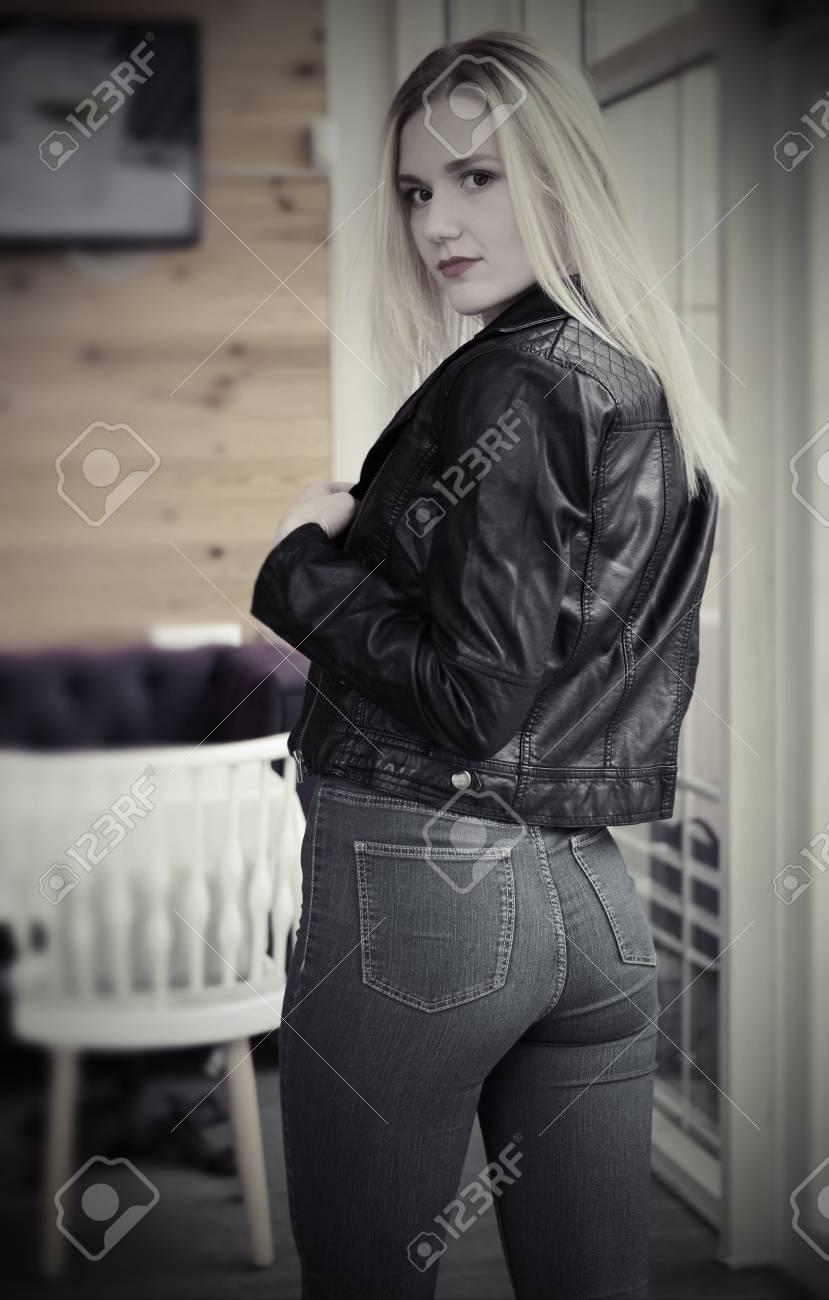 2fb8963b90c Beautiful young blonde woman posing in cafe. She wears a black..