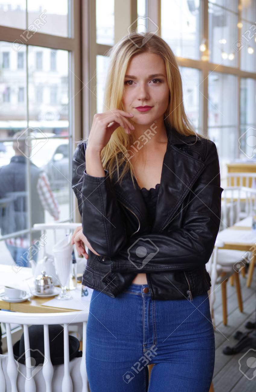 7a88e0d1282 Beautiful young blonde woman posing in cozy cafe. She wears a..