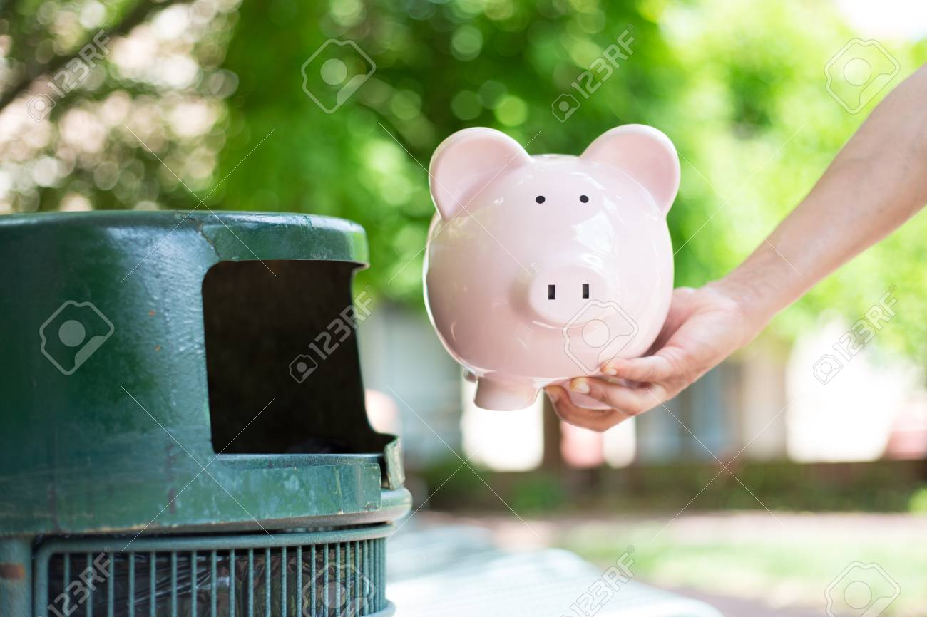 closeup cropped portrait of someone hand tossing piggy bank into