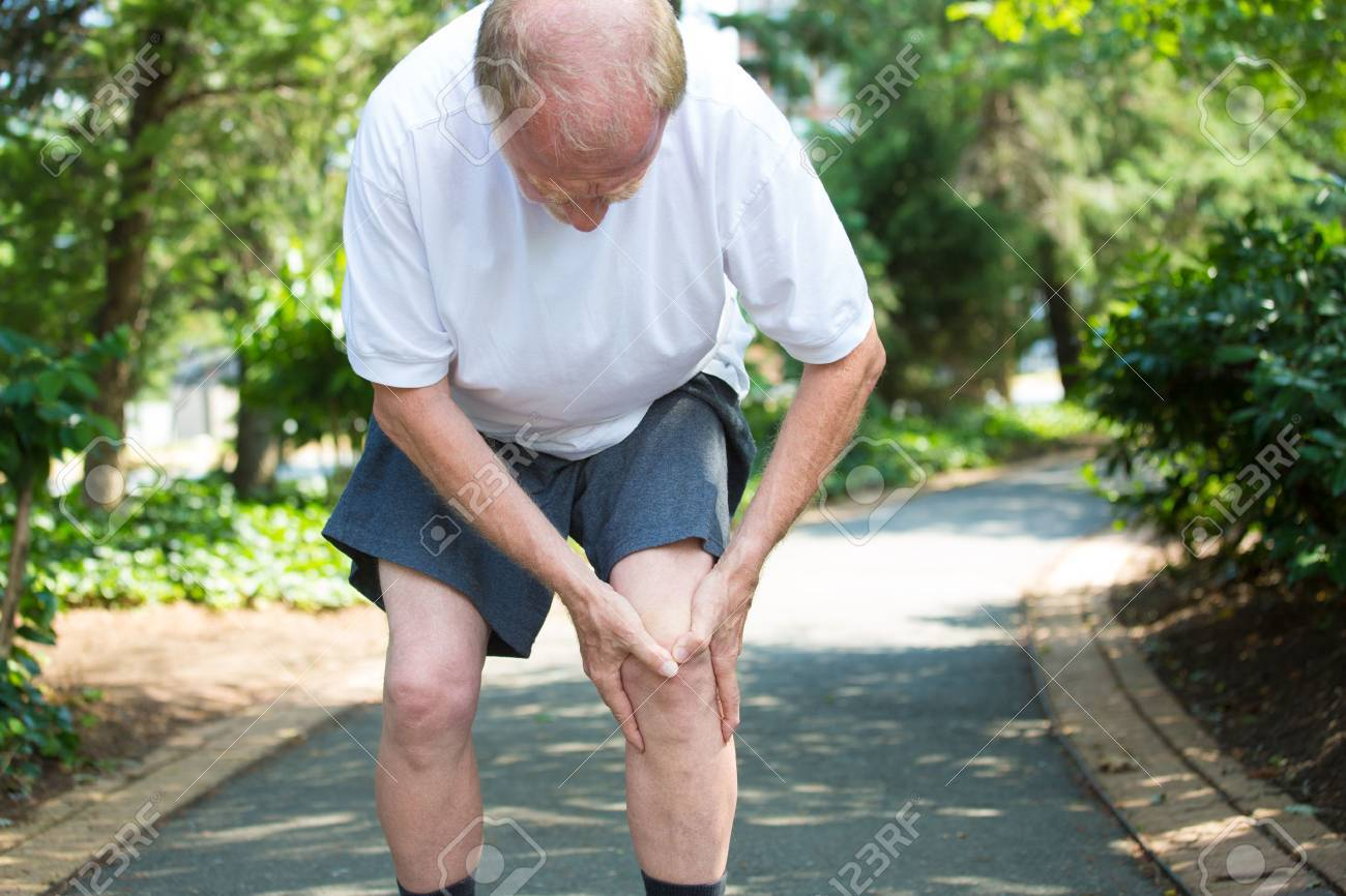 Ritratto del primo piano, uomo più anziano in camicia bianca, pantaloncini grigi, in piedi su strada asfaltata, in forte dolore al ginocchio, alberi