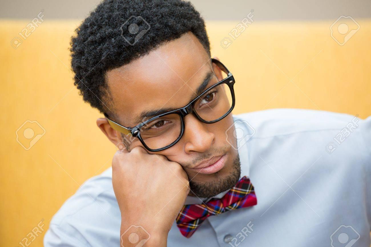 Banque d images - Portrait Gros plan, jeune perturbé, affligé geek avec de grosses  lunettes noires, noeud papillon et chemise bleue, main sur la joue ... 59ffb0b0048f
