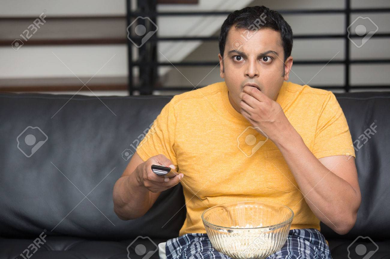 Closeup portrait, young man in yellow t-shirt, sitting on black leather couch, watching TV, holding remote, surprised at what he sees, munching popcorn, isolated indoors flat background - 47857647