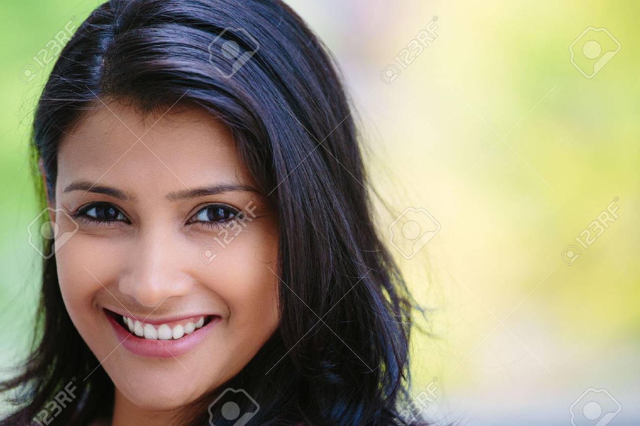 Closeup headshot portrait of confident smiling happy pretty young woman, isolated background of blurred trees. Positive human emotion facial expression feelings, attitude, perception - 48738663