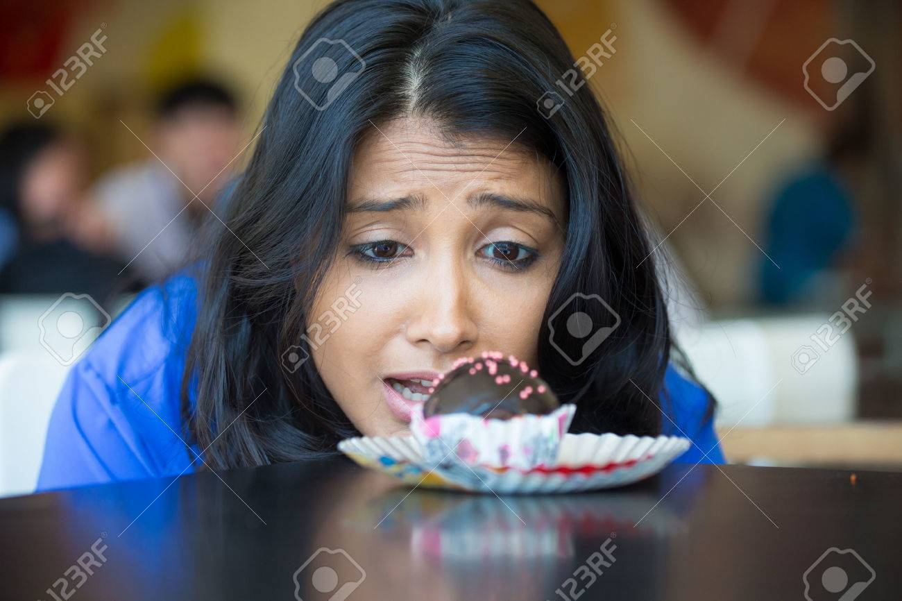 Closeup portrait of desperate woman in blue shirt craving fudge with pink sprinkles dessert, eager to eat, isolated indoors background - 51897791