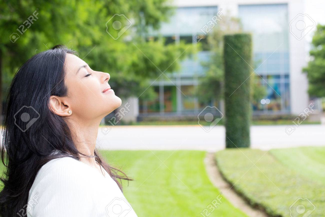 Closeup portrait, young woman in white shirt breathing in fresh crisp air after long day of work, isolated outdoors outside background. Stop and smell the roses, connect with nature - 60873944