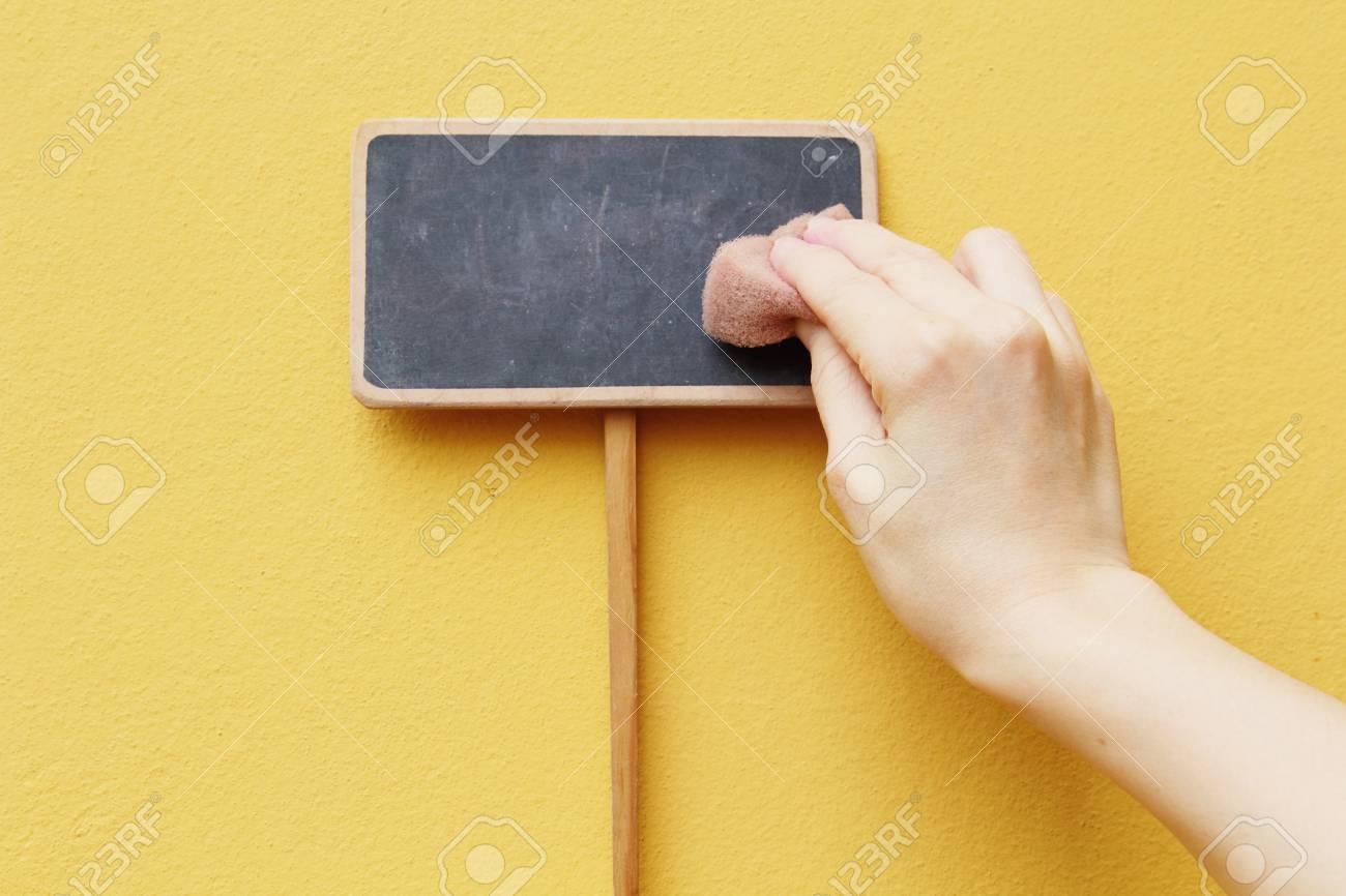 A hand erasing on chalkboard Stock Photo - 12902073