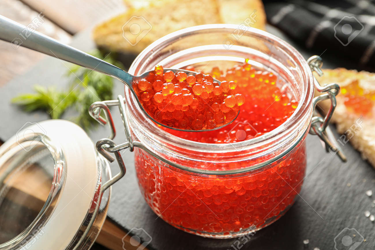 Composition with caviar in glass jar, bread, spoon, towel and cutting board, space for text - 125887702