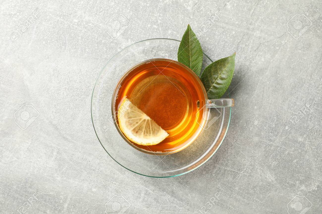 Cup of tea, mint and lemon on grey background, top view - 130085541