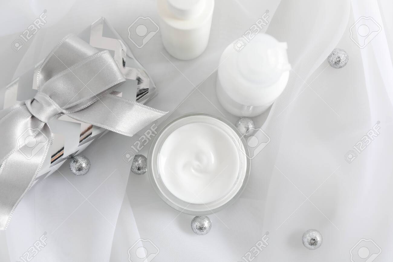 Set cosmetics, jar of winter cream for skin, gift boxes on white fabric background, closeup. Top view - 135192922